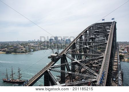 SYDNEY,NSW,AUSTRALIA-NOVEMBER 20,2016: Sydney Harbour Bridge, three-masted tall ship and tourists climbing steel arch overlooking cityscape in Sydney, Australia.