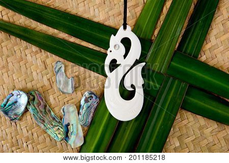 New Zealand - Maori Themed Objects - Carved Bone Pendant With Shells On Flax Leaves And Woven Backgr