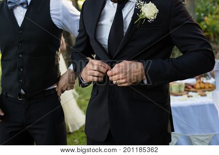 Mid-section of bridegroom buttoning a wedding suit