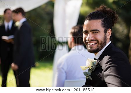 Portrait of handsome groomsman smiling in park during wedding