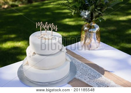 Decorated wedding cake on table in park
