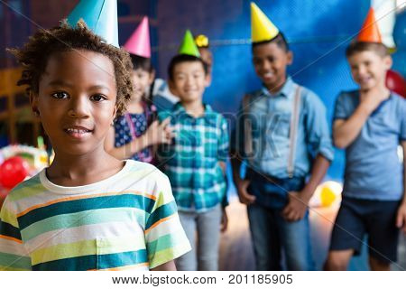 Portrait of girl wearing party hand with friends in background during birthday party