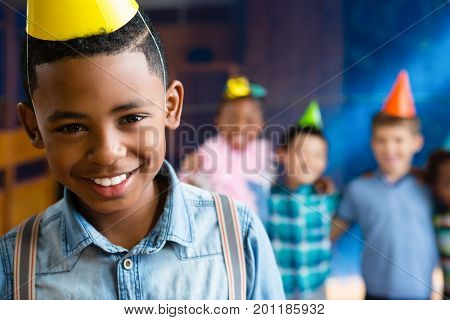 Portrait of boy wearing suspenders with friends in background during birthday party