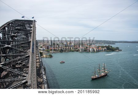 SYDNEY,NSW,AUSTRALIA-NOVEMBER 20,2016: Sydney Harbour Bridge arch with bridge climbers and tall ship in harbour in Sydney, Australia.