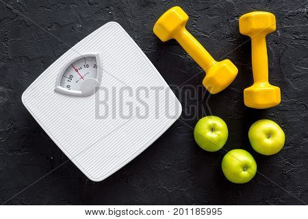 Sport and diet for losing weight. Bathroom scale, apple and dumbbell on black background top view.
