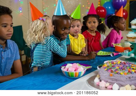 Girl whispering to boy at table during birthday party