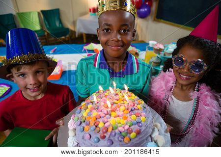 High angle portrait of boy holding birthday cake while standing with friends