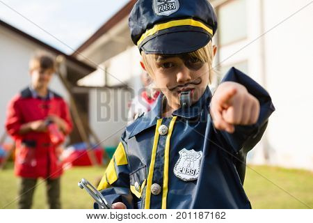 Portrait of boy in police costume gesturing while standing in yard
