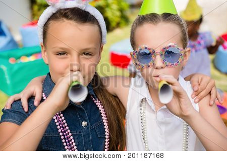 Close up portrait of girls blowing party horn while standing in yard during birthday