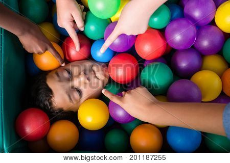 Cropped hand on children pointing on boy playing in ball pool
