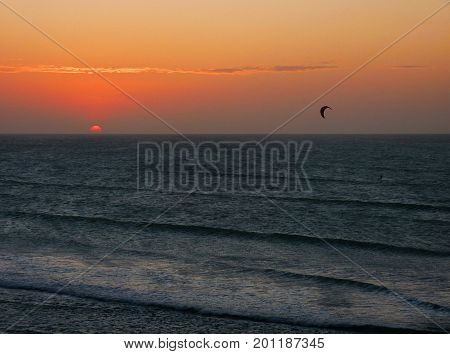 Kitesurfing at sunset Deep sea sunset with a kitesurfer. Dark blue sea and orange sky The sun is disappearing over the horizon on the left and a black kite is flying on the right. The picture was taken in Jericoacoara Brazil