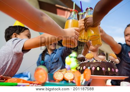 Close up of children toasting juice during birthday party