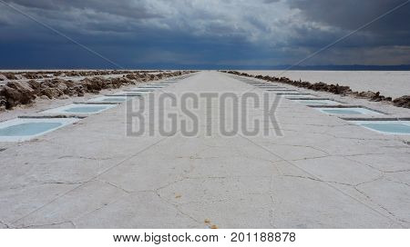 White salt harvesting pools in the middle of a huge salt flat. The rainy clouds have already pass the Andes and are coming closer. The picture was taken in Salinas Grandes Argentina