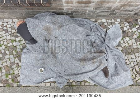 Elevated View Of Homeless Man Covered With Blanket Sleeping On Street