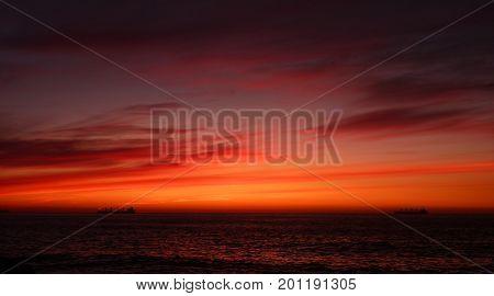 Sunset in Vina del Mar Chile Two ships on a dark orange sea.