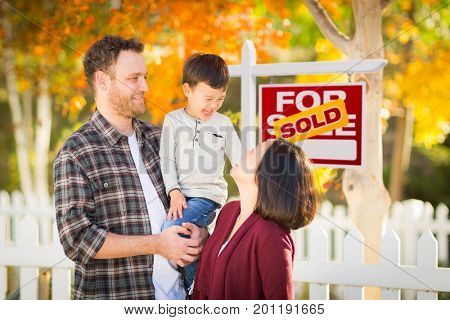 Young Mixed Race Chinese and Caucasian Family In Front of Sold For Sale Real Estate Sign and Fall Yard.