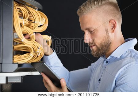 Close-up Of Young Male Technician Checking Server's Wires In Data Center
