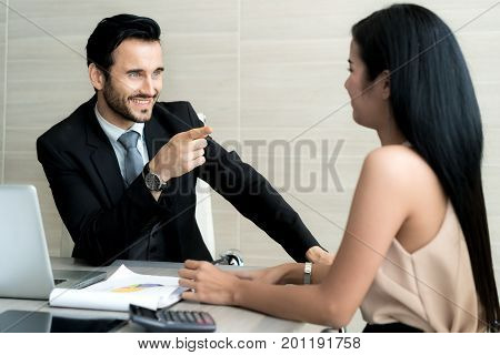 Young Businessman boss talking to employee pointing to employee businessman discussing with partner and have question to Subordinate in meeting.