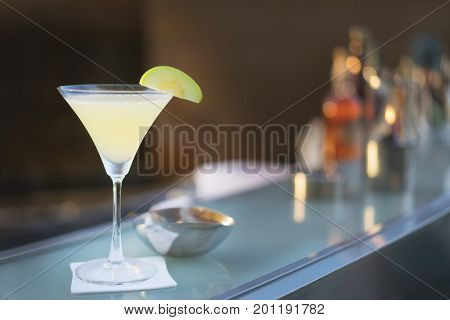 Alcoholic cocktail apple martini shot at bar with counter bar in background.