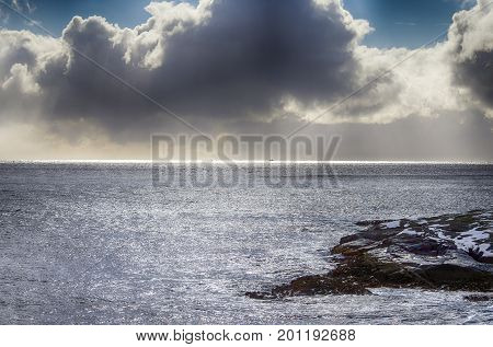 Amazing Slim Line of Sunlight of Sun Going Down On Horizon Over the Ocean at Lofoten Islands in Norway. Against Grey Cloudy Skies.Horizontal Image