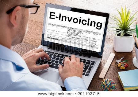Cropped image of businessman preparing e-invoicing bill on laptop at desk in office