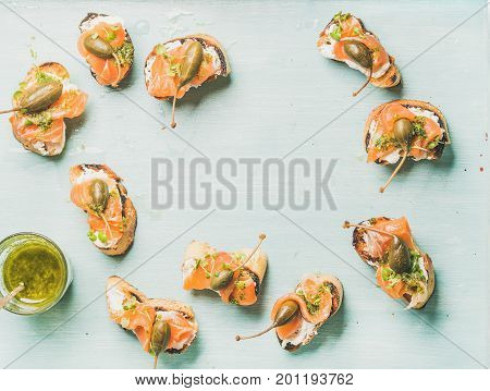 Crostini with smocked salmon, pesto sauce in glass, watercress and capers over light blue background, top view, copy space, flat-lay. Party, catering or fingerfood concept