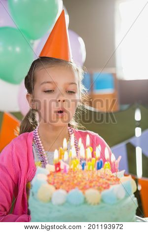 Birthday girl blowing birthday candles at home