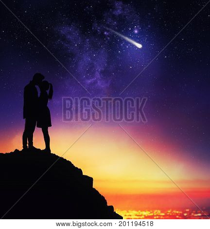 Couple of lovers in backlight from above a mountain expresses a desire during the sight of a falling star