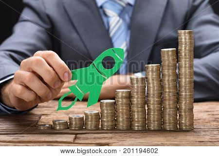 Midsection of businessman holding green paper rocket on stacked coins arranged in increasing order