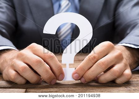 Midsection of businessman holding paper question mark at wooden table