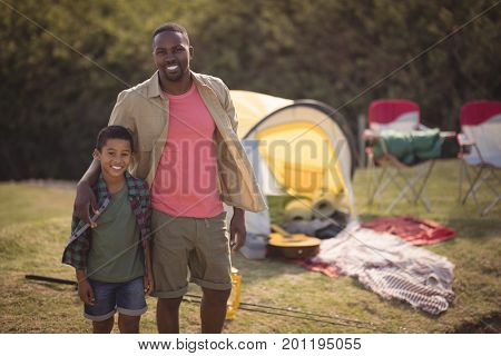 Smiling father and son standing with arm around in park