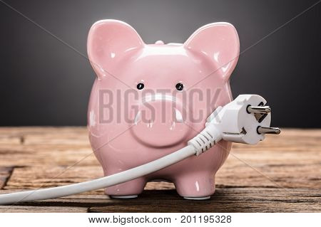 Closeup of piggybank with plug on wooden table against black background