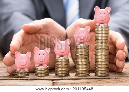 Midsection of businessman protecting piggybank on stacked coins in increasing order