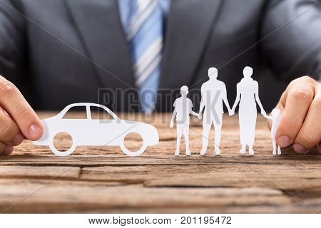 Midsection of businessman holding paper car and family on wooden table