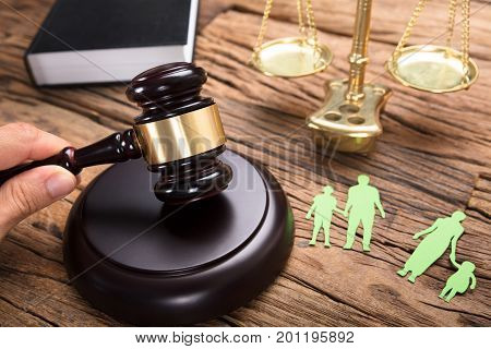 Judge hitting mallet by separated paper family and justice scale on wooden table