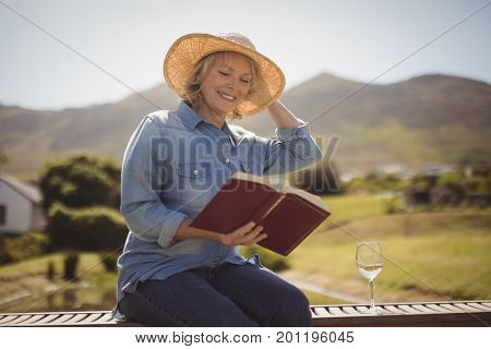 Smiling senior woman reading a book on park bench