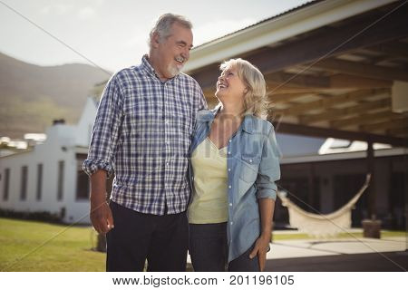 Smiling senior couple standing together in garden on a sunny day