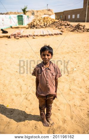 RAJASTHAN INDIA - MARCH 07 2016: Vertical picture of native indian boy posing in Thar Desert located close to Jaisalmer the Golden City in India.