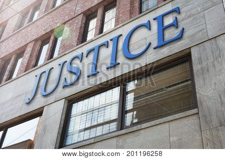 Low angle view of justice sign on modern building in city