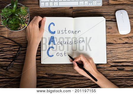 Elevated View Of A Businessperson Writing Customer Acquisition Cost Concept On Notebook