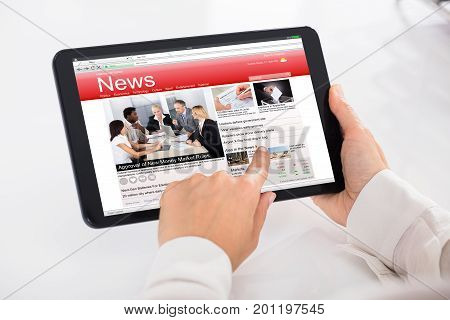 Close-up Of A Person Reading News On Digital Tablet