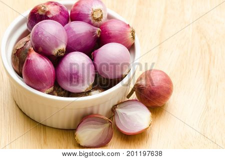 Fresh shallots in a bowl on wooden background, food ingredient, spices and herbs