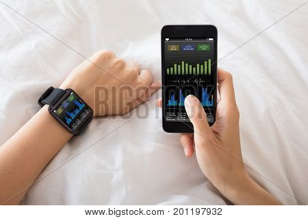 Close-up Of A Female's Hand With Smart Watch And Mobile Phone Showing Heart Beat Rate