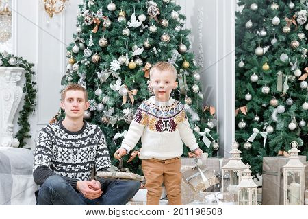 Happy young father and litle boy in Christmas morning in home. Christmas tree on the background. look at the camera. Happy new year Young parents with a small child