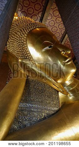 BANGKOK, THAILAND--Close up of the face of the Golden Reclining Budhha at Wat Pho Temple in Bangkok, Thailand, taken in March 2016. Wat Pho is also known as Wat Phra Chettuphon Wimon Mangkhlaram Ratchaworamahawihan.