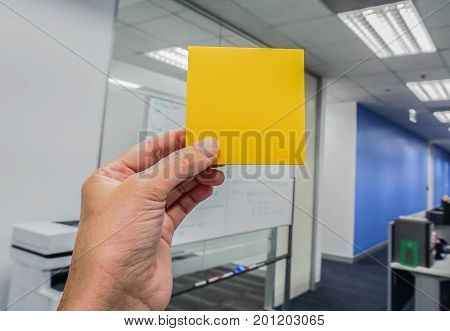 businesswomen hold mock up orange posit with left hand in office