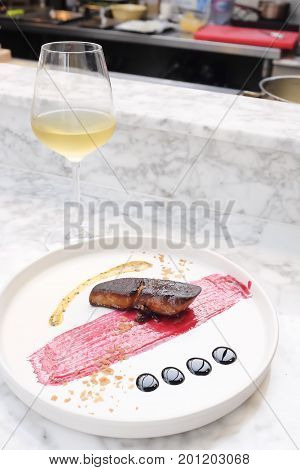 Pan seared Foie Gras steak and red berries sauce with beautiful decoration in fine dining style on a marble table. The background is the open kitchen. The dish is serving with white wine