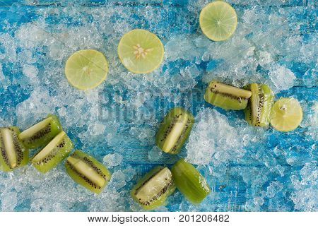 Crushed Ice Cubes And Lemon, Kiwi, Wooden Spoon On Vintage Blue Wooden Table. Top View