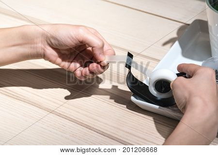 Lady Hands Pulling Scotch Tape From Scotch Tape Dispenser