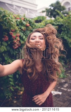 Laughing young Vietnamese woman with flattering hair taking selfies outdoors
